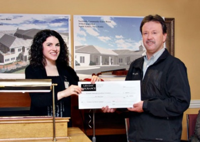 Reg Day, of Less Day Insurance, presents Fundraising Coordinator Lisa MacNeil with a 5000.00 cheque.