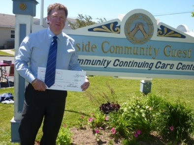 "Peter Walsh of W.J. Dooley Funeral Home presents a generous cheque of 3000.00 to the ""Complete the Dream"" campaign. July 9, 2010"