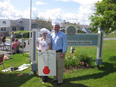 Fundraising Coordinator, Lisa MacNeil with MLA Cecil Clarke holding the Complete the Dream Campaign thermometer.  August 13, 2010